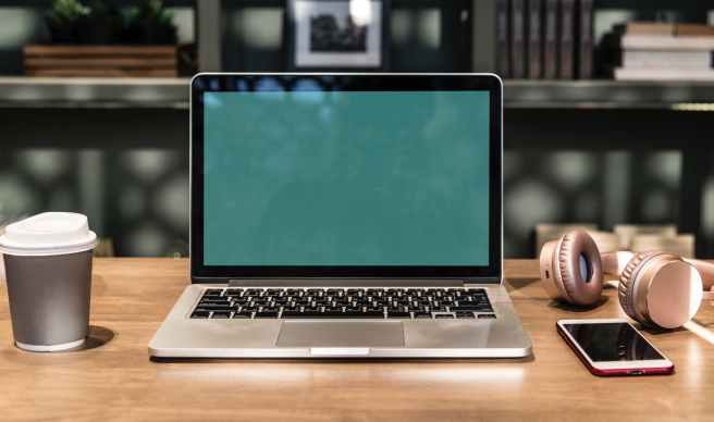 close up photography of macbook near mobile phone and headset