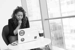 grayscale photo of woman facing macbook