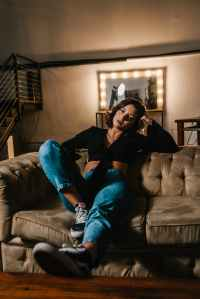 photo of woman sitting on a sofa posing